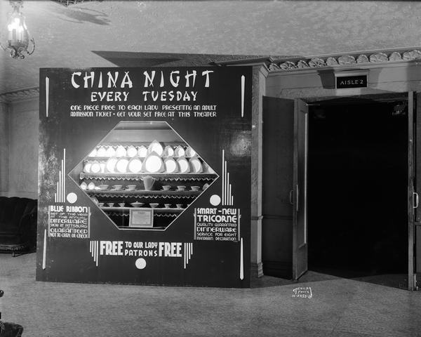 "Promotional display of Salem china, Tricorne pattern, in the lobby of the Eastwood Theatre, 2090 Atwood Avenue. The sign reads: ""China Night Every Tuesday - One Piece Free to Each Lady Presenting an Adult Admission Ticket - Get Your Set Free at this Theater."" ""Blue Ribbon Set of the Year at the Annual Dinnerware Show at Pittsburgh - Guaranteed not to Craze or Check."""