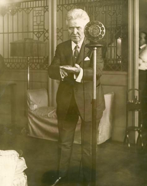 Independent presidential candidate Robert M. La Follette, Sr., standing behind a radio microphone delivering a Labor Day address.