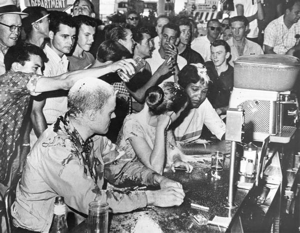 Civil rights sit-in by John Salter, Joan Trumpauer, and Anne Moody at Woolworth's lunch counter. People pour sugar, ketchup and mustard on them in protest. Looking on as part of the crowd are Red Hydrick, seen in the upper left wearing a hat and eyeglasses, and teenager D. C. Sullivan, who is in the middle of the crowd smoking a cigarette.