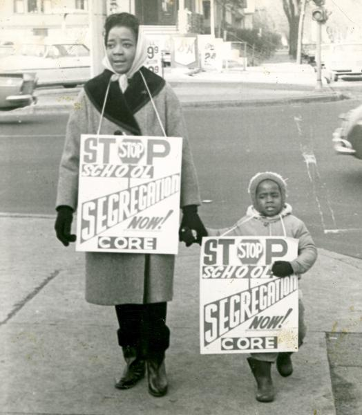 A woman and child carry CORE picket signs protesting school segregation.