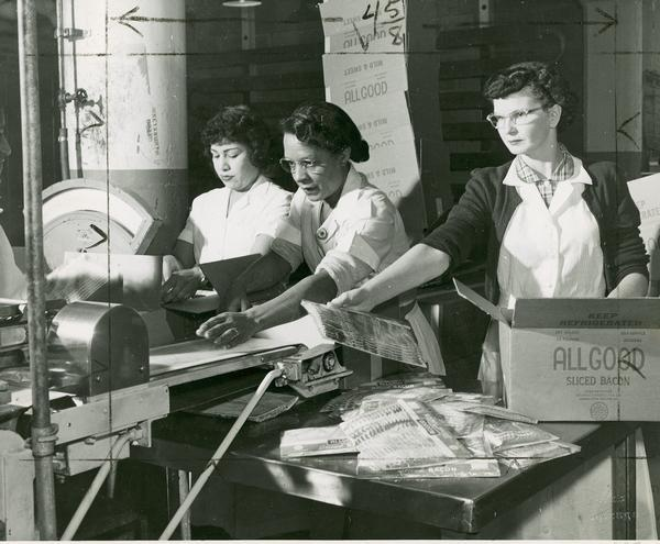 "Three women packing ""All Good"" brand bacon."