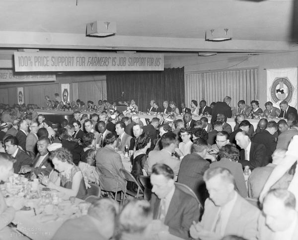 "An integrated banquet hall during the Ninth Convention in Sioux City, Iowa. There is a banner overhead that reads ""100% Price Support For Farmers Is Job Support For Us""."