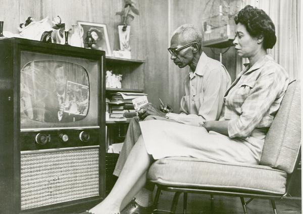 L.C. and Daisy Bates watching television with Arkansas Governor Orval Faubus on the screen.