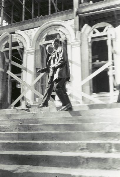 Colonel Charles Lindbergh walking along steps at the Memorial Union, at the University of Wisconsin-Madison. Mr. Carl Johnson (left) of the Union Committee made the presentation. The building appears to be under construction.