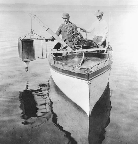 Edward A. Birge and Chancey Juday with plankton trap in Lake Mendota. From album of photographs relating to the research in limnology conducted at Trout Lake, and elsewhere by Edward A. Birge, University of Wisconsin-Madison.