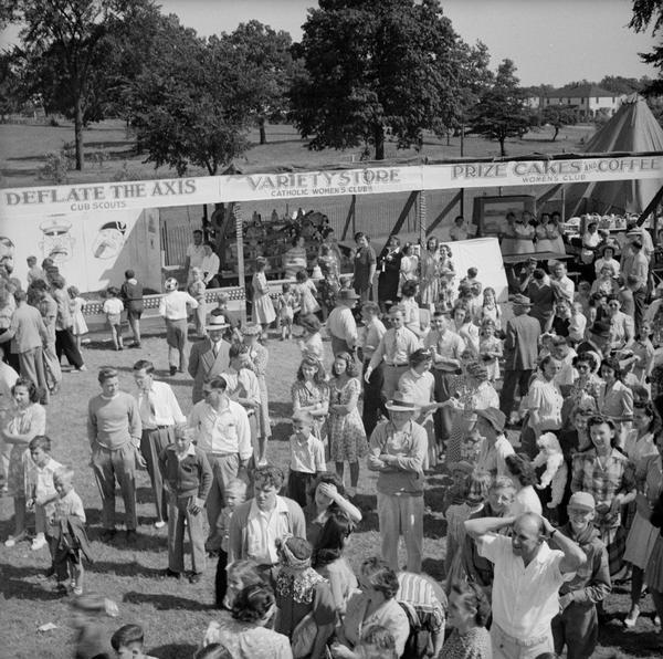 "Slightly elevated view of crowd gathered at a Civilian Defense Rally. Booths are in the background, including a game booth where you can ""Deflate The Axis,"" featuring caricatures of WWII villains to be used as target practice which is being run by the Cub Scouts, a ""Variety Store"" run by the Catholic Women's Club, and a ""Prize Cakes & Coffee"" booth run by the Women's Club."