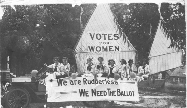 "Members of the Oshkosh Equal Suffrage League in their 4th of July float made up with a sail boat. Banners read ""Votes for Women"" and ""We are Rudderless, We Need The Ballot."" Identified in the picture are Lilian Clark, Bernice Mocke, Helen West, Gertrude Hull, Josephine Van Slyke, Hester Lancaster, Katherine Forward, Jennie Robinson, and Maria Hilton."