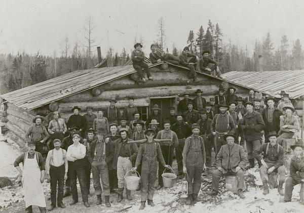 Lumber crew posed in front of a building at Ole Emerson's lumber camp.