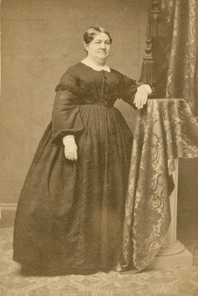 Formal full-length studio portrait of Elizabeth Therese Baird wearing a long, black dress.