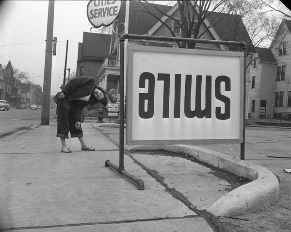 "Filling station sign reading: ""smile,"" purposely put upside down. A young woman is bending over to read it."
