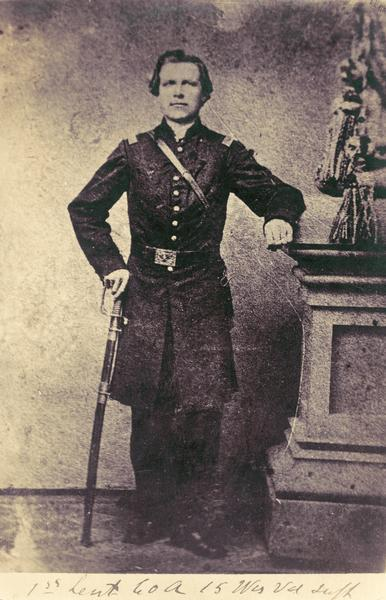 Full-length studio portrait of Civil War soldier Nils (Niels) J. Gilbert, Company A, of the 15th Wisconsin Infantry, believed to have been taken in October 1864 at Chattanooga, Tennessee.  He is in uniform and leaning on his sword. He entered service on 2 October 1861 as a 1st Sgt, was promoted to 1st Lt. on 19 October 1864, and mustered out on 20 December 1864 when his term expired.