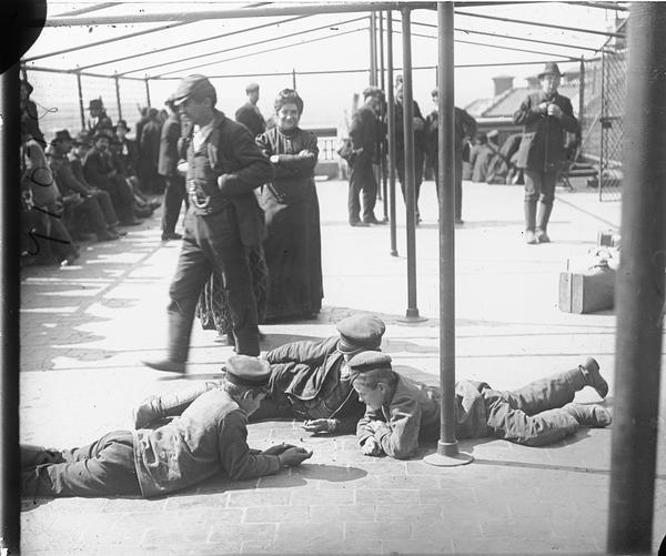 Immigrants being detained at Ellis Island. Three boys lay on the ground together.