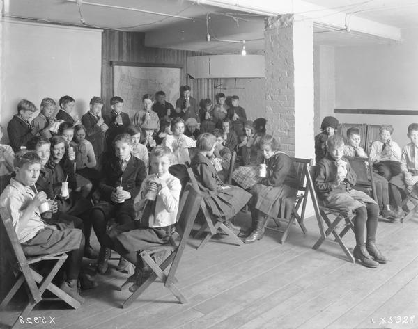Classroom full of school children drinking milk at Washington school.