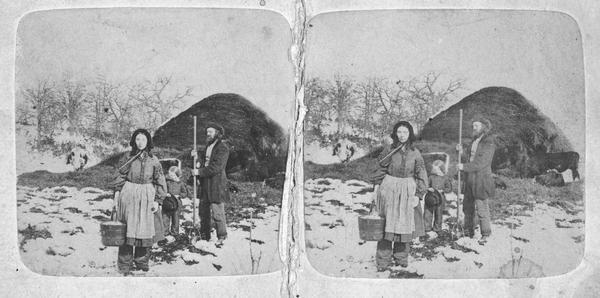 Stereograph (also known as a stereoview) of woman, man and child outdoors on a farm with snow on the ground. The woman is wearing bloomers and is holding a bucket in the process of doing chores, the man is holding a pitchfork, and the child is holding a hat. In the background are cows eating near a large pile of hay.
