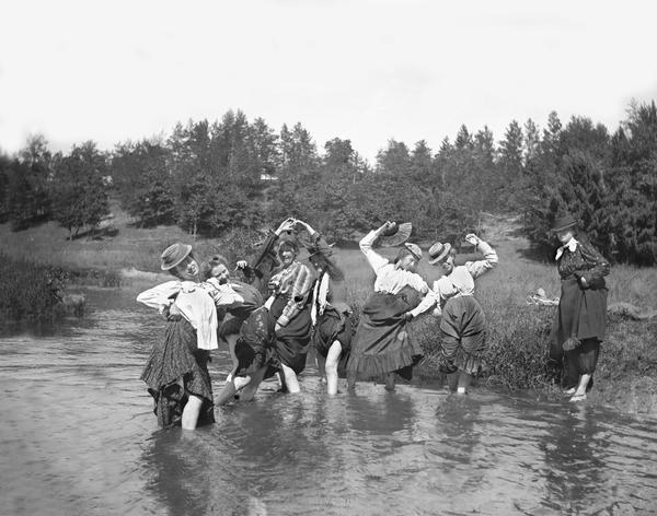 Group of women in comical poses pulling up their skirts while standing  in a stream. One woman stands on the river bank on the right. Behind them is a hill with trees.