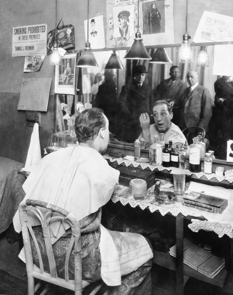 Ed Wynn is shown in his dressing room applying makeup at the mirror. Reflected in the mirror left to right are Wynn's manager Fred R. Zweifal, Wynn's valet, and George W. Lederer.