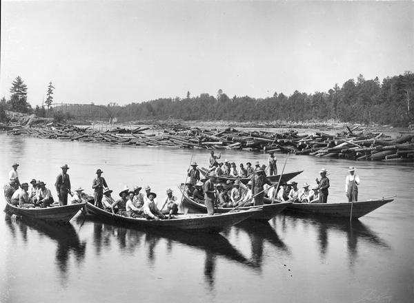 Log driving crew on river in five bateaux. In the background on the left is a bridge.