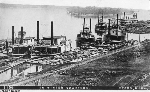 Elevated view of nine rafters wintering at Reed's Landing. At left is <i>Hiram</i> Price, with <i>L.W. Crane</i> beside her. Third is <i>Annie Girdon</i> with the <i>Union</i> behind her. Alongside the <i>Annie Girdon</i> is the <i>L.W. Barden</i>. Next to the <i>Union</i> is the <i>Clyde</i>, and next to it is a boat believed to be the <i>St. Croix</i>. At the extreme right is the <i>Silas Wright</i>, the only sternwheel rafter, all the rest are sidewheel rafters. Along the shoreline is a large raft of lumber.