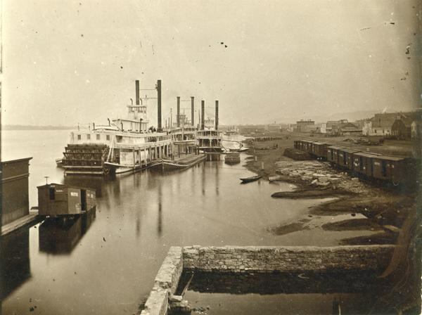 "The sternwheel packet, ""Arkansas,"" next to a barge with other steamboats at the levee in Winona between 1870 and 1880. Railway cars are on a siding in the yard next to the levee."