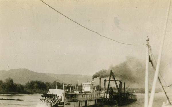 "The ""Clyde"" after being converted to a sternwheel rafter, pushing a tow with a locomotive on board."