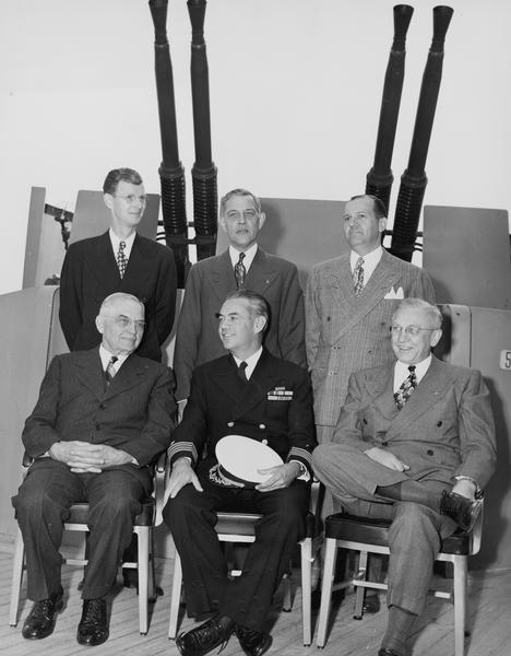 "Members of the official Silver Presentation Delegation on board the USS ""Wisconsin"". Bottom left to right: Judge Rosenberry, Captain Roper, and Oscar Rennebohm Standing left to right: E.N. Doan, William Schwanke, and John Dickinson."