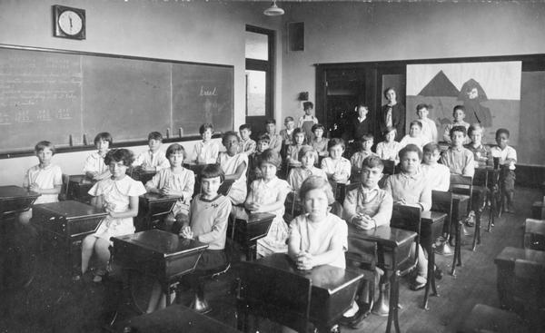 View of the Longfellow School's 4th grade class seated at their desks as their teacher stands at the back of the classroom.