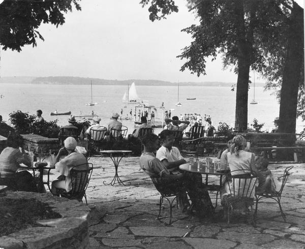 Summertime view of people at tables on University of Wisconsin-Madison Memorial Union terrace, looking out to canoes and sailboats on the lake. People wearing bathing suits stand on a pier.