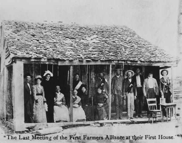 The first Farmers Alliance - also known as the Southern Alliance - is shown in front of the cabin in which their first formal meeting was held in 1877 in Pleasant Valley, Lampasas County, Texas. The cabin was uprooted and exhibited in the Chicago Exhibition of 1893. Later it was chopped up and pieces were passed out to the Populist partisans.