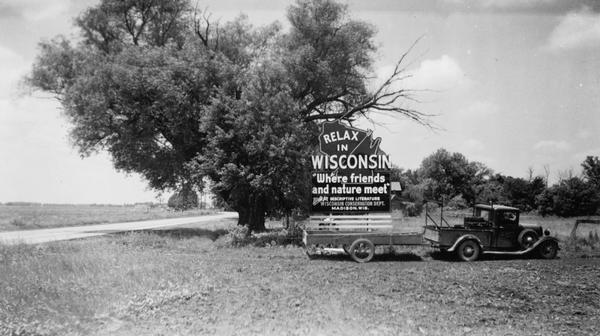 "A movable billboard aimed at passing motorists along State Highway 20 in Illinois.  It reads ""Relax in Wisconsin, Where Friends and Nature Meet.""  Although tourists traveled to Wisconsin by train during the nineteenth century, the advent of personal automobiles greatly expanded the tourist sector of the economy.  This billboard was sponsored by Wisconsin's Conservation Department which was then responsible for state tourism promotion."