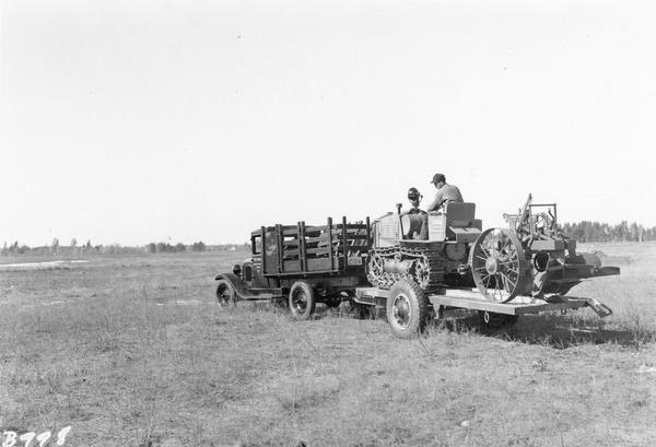 A tractor and plow on a trailer is being towed by a truck.