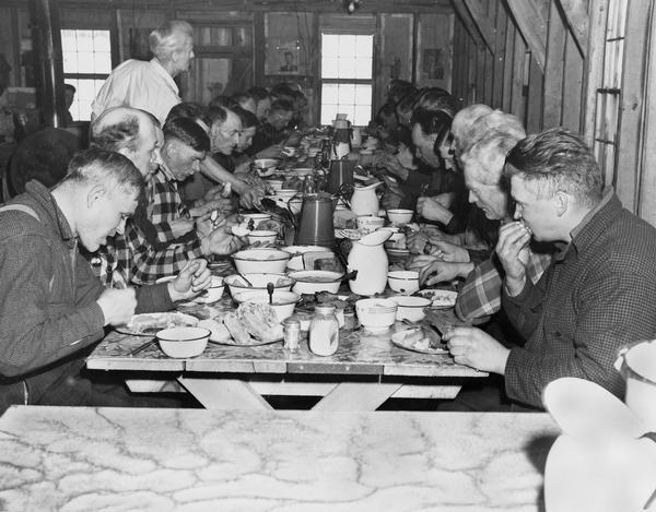 Lumberjacks eating in a cook shanty; probably early twentieth century.