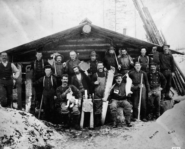 Camp Montana loggers pose in front of camp building with their tools.  Includes a dog sitting on the lap of one logger.