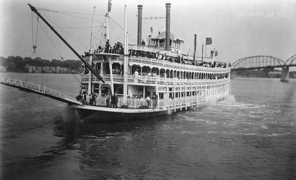 A bow view of the sternwheel excursion, <i>J.S.</i>, near Lyons, Iowa (now called Clinton) with an excursion party aboard taken between 1901 and 1910. Bridge in background.