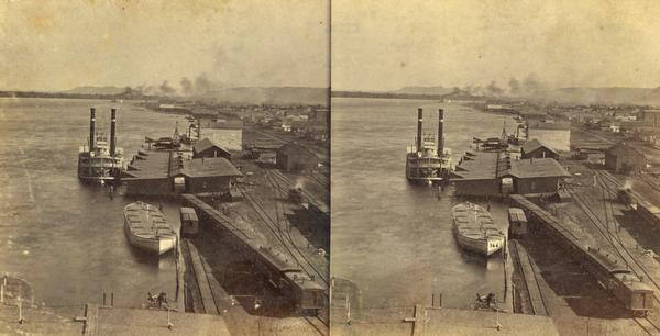 "Elevated view of the sidewheel packet, ""Keokuk,"" at the Winona, Minnesota levee between 1858 and 1866. A barge and railway cars are in the foreground."