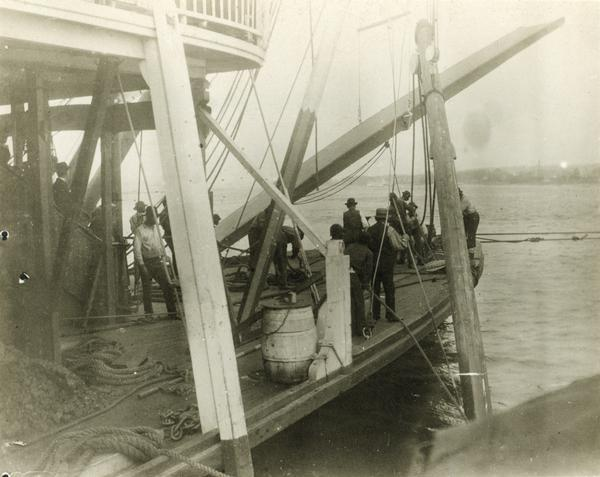 The sidewheel excursion, <i>Saint Paul</i>, after running aground near Muscatine. The spar is set and the line out. Dan Sauer, the carpenter, is holding the sounding pole. The sidewheel was later named the <i>Senator</i>.