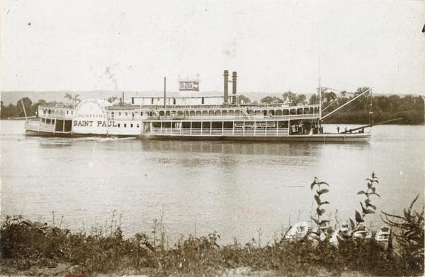 "The sidewheel excursion, ""Saint Paul,"" on the Mississippi River near Lansing, Iowa. Small boats drawn up to bank in foreground. Later named ""Senator."""