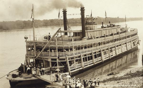 The sternwheel excursion, <i>Sidney</i>, later named <i>Washington</i>, landing at Bellevue. Passengers are disembarking. A sign on the ship reads Streckfus Lines.
