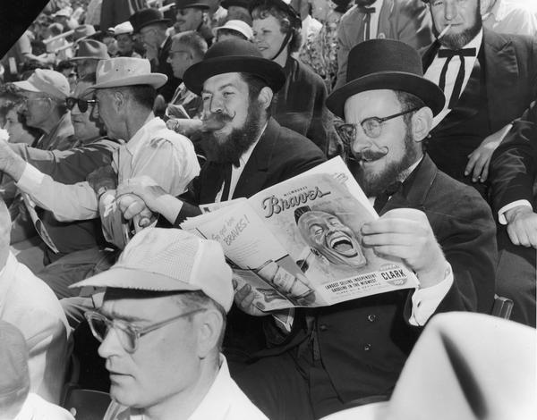 Two men sitting in the stands review the Milwaukee Braves official program during a game.