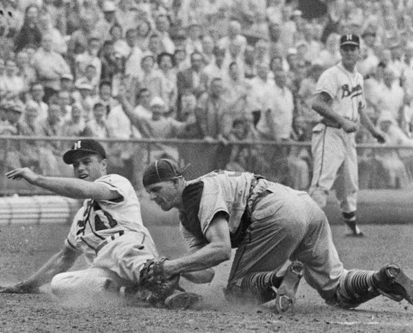 Eddie Mathews, third baseman for the Milwaukee Braves baseball team, slides into home plate. Chicago Cubs catcher Cal Neeman applies the tag as Braves third base coach, Connie Ryan looks on.