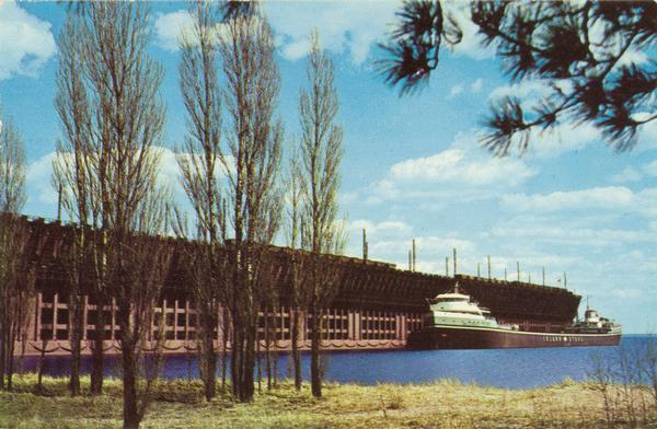 The screw bulk freighter, Wilfred Sykes at L.S. and I. Ore Dock in Marquette, Michigan about 1960. Lake shore and trees in the foreground.