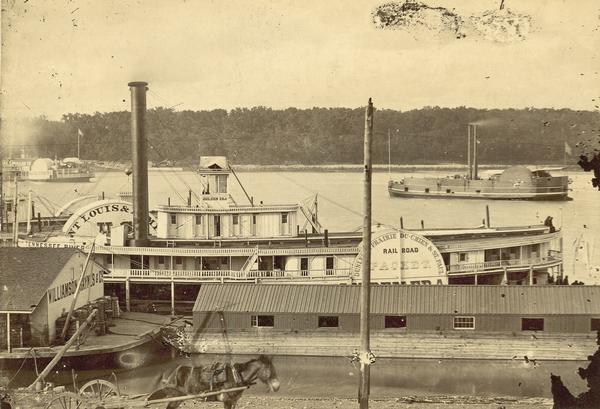 "Elevated view of the steamboat ""Golden Era,"" which did service during the Civil War, docked near buildings. It was sold to Michael Purcell of New Orleans in 1866 and abandoned in 1868."