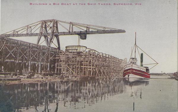 Colorized image of the frame of a large boat being built at the shipyards in Superior.