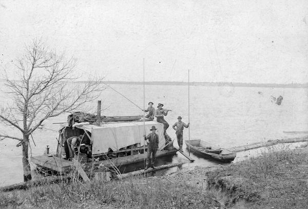 Five lumberjacks, one of whom is playing the fiddle, pose by a docked riverboat with a rowboat nearby.