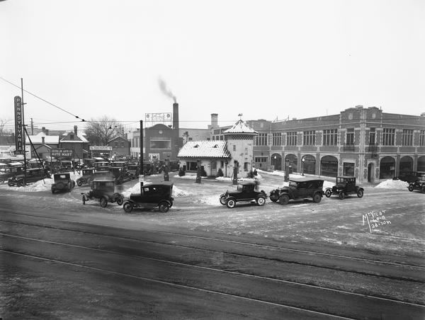 "Elevated view of cars lining up at Pennco filling (gas) station at the corner of State and Gorham Streets to get free crankcase draining and ""Oak"" Motor Oil offered during a winter cold snap."