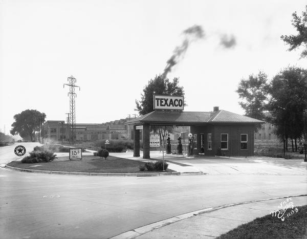 "Bondi & Sachtjen Texaco service station, 1462 E. Washington Avenue at Thornton Avenue, with Fuller & Johnson buildings in the background. Text with print reads: ""Bondi & Schtjen Texaco Stsation, 1462 E. Washington Avenue. View looking toward Capitol. Fuller & Johnson Mfg. Co., 1402-44 E. Wash. Ave."""