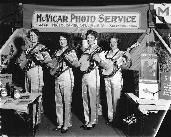 Four women are playing banjos in the McVicar Photo Service Booth at the 1930 East Side Businessman's Association (ESBMA) Fall Festival.