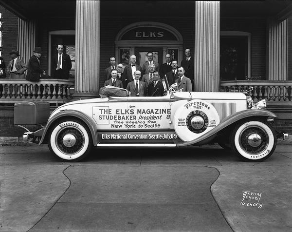 """Elks Magazine purple and white free wheeling Studebaker President 8 roadster convertible parked in front of the Elks Club, 120-124 Monona Avenue. The car's crew is posing with local men who welcomed them. The automobile has a sign that reads: """"The Elks Magazine - Studebaker President 8 - free wheeling from New York to Seattle."""""""