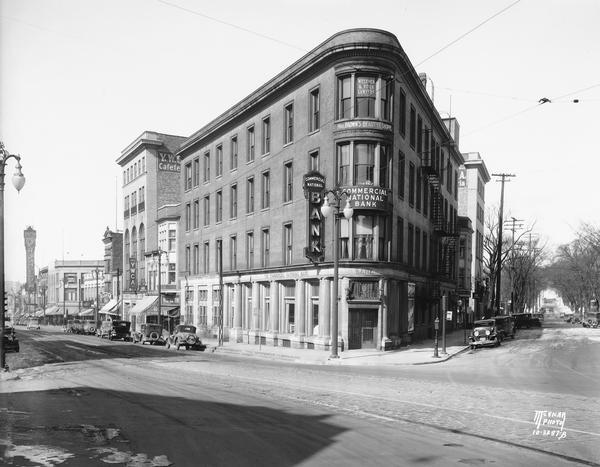 The Commercial National Bank building, on the corner of State and Carroll Streets, housed the bank as well as Mrs. Brown's Beauty Shoppe and Wegener and Roick Lawyers. On the right is a view down Carroll Street towards Lake Mendota. On the left down State Street among many other storefronts is the Palace Drug Store, the YWCA, and the marquee for the Orpheum Theatre.