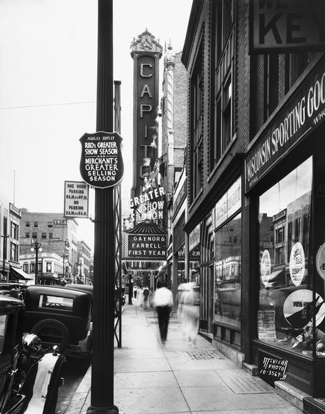 "Pedestrians (in motion) are walking down State Street towards the Capitol building, near the Capitol Theatre marquee, RKO sign, the YWCA, Oettings Restaurant and Wisconsin Sporting Goods store. Text with print: ""Looking east along 200 block of State St."""