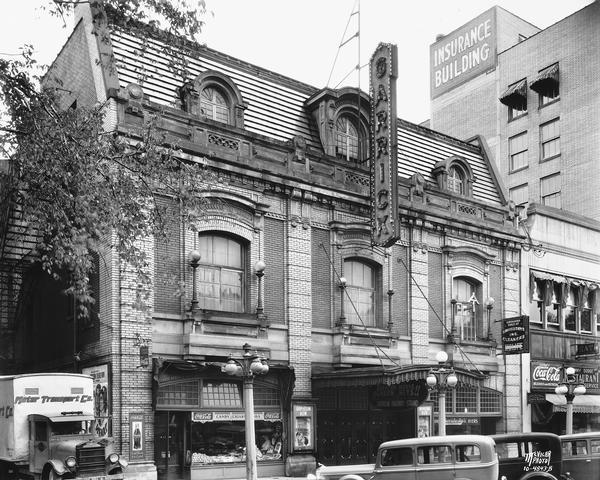 Exterior view of the Garrick Theater at 115 Monona Avenue. The view also contains the Kehoe Cigars store, Savidusky's at 113 Monona Avenue, Jimmy Dodge Billiards & Restaurant at 117 Monona Avenue, and a Motor Transport Co. truck.